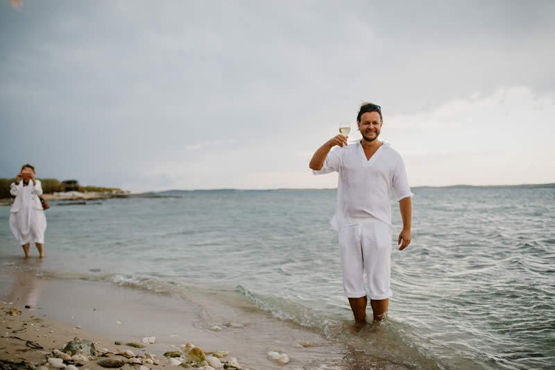 island wedding groom beach sand
