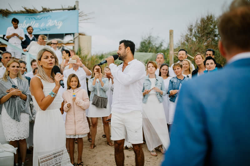 people singing in a beach wedding