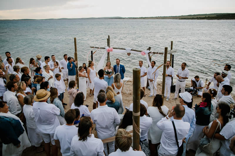 guests gathered on the beach for a wedding